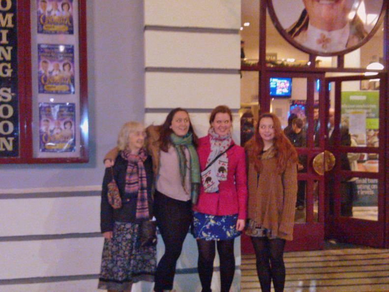 Girls and Grandma standing outside the theatre.
