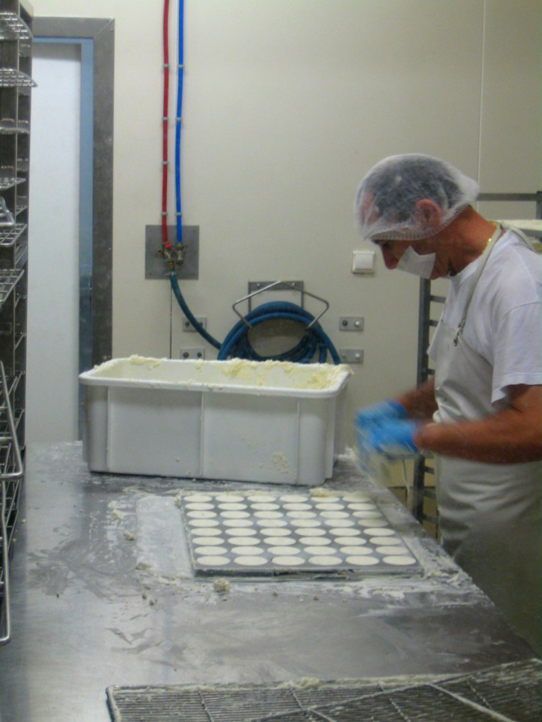 the finished curds are pressed into a mold, which is then easily lifted off to reveal perfect rounds.
