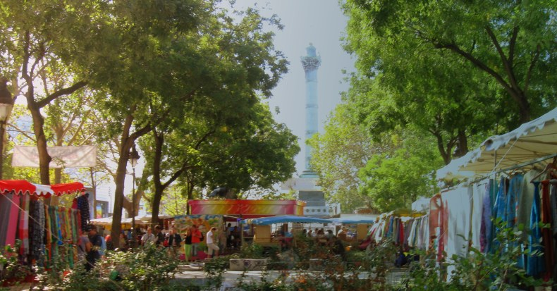 merchants sell their wares in brightly colored tents during market days, with the Bastille monument towering in the background